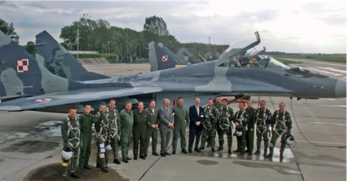 "On August 27th 2012, the 23rd Air Base was visited by Philip Methuen-Feric and Witold Urbanowicz Jr., the sons of two great pilots of the 303rd Squadron. In the picture, they are posing with the modern pilots in front of the MiG-29 no. 111; between the two sons stands the commander of the 23rd BLT, Col. Maciej Trelka. The plane was the first ever painted air craft as part of the ""Warsaw Scythemen"" project. Its patron became Mirosław Ferić – a fighter ace (photo: Wojtek Matusiak)"