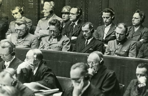 The so-called trial of the doctors in front of the American court martial in Nuremberg (<i>US vs. Karl Brandt and others</i>), 1946 – 1947. 9 out of 23 accused criminals sit at the court room. They are probably (from the left): in the first row Karl August Genzken (?), unknown, unknown, Joachim Mrugowsky; in the second row Hermann Becker-Freyseng, Georg Weltz, Konrad Schäfer, Waldemar Hoven (?), Wilhelm Beiglböck. In the foreground sit the defenders of the accused in robes.